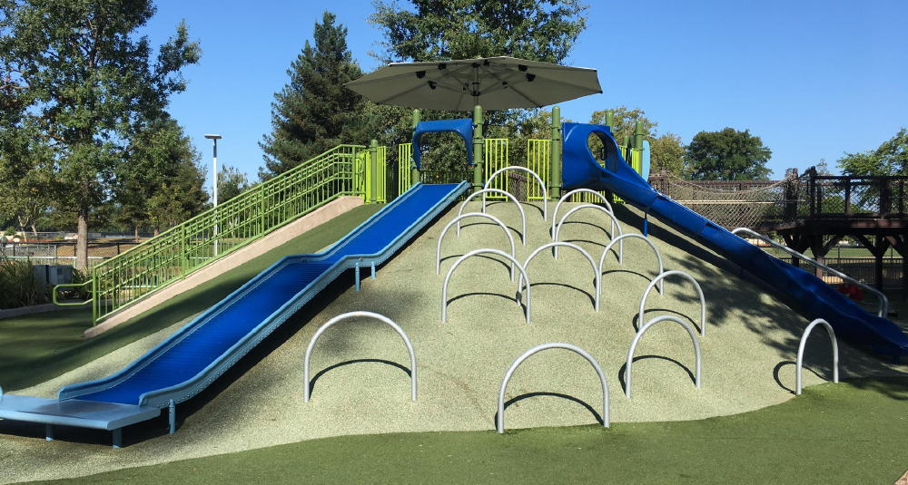 climbing loops next to dual slides at playground